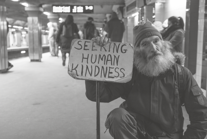 "man holding a sign ""seeking human kindness"""